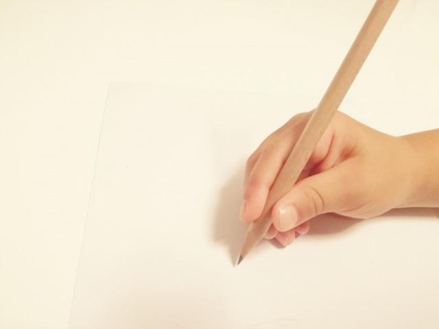 鉛筆を持つ子どもの手
